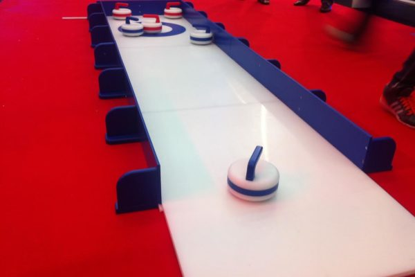 activities gallery with Ice Curling rink indoors with curling stones, teams competing agianst each other to get the curling stone as close to the cntre of the lane as possible to score the most points